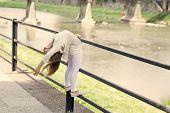 Kid Girl Bends Backwards As Flexible Gymnast Near Railing At Riverside Background. Girl Kid Gymnast  poster