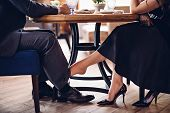 Girl Flirts With A Guy In A Restaurant. She Touches His Leg With Her Bare Foot Under The Table poster