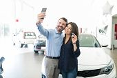 Hispanic Couple Photographing Themselves To Post On Social Media While Standing By New Car In Showro poster