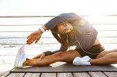 Image of a beautiful young sports fitness woman make stretching exercises at the beach outdoors list poster