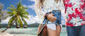 summer, fashion and people concept - close up of young hippie couple over tropical beach background  poster
