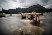 Fly Fishing The Cold Rivers In The Canadian Rocky Mountains For Trout Is The Ultimate Adventure poster