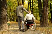 stock photo of disabled person  - Husband and handicapped wife taking stroll in park alley in fall time - JPG