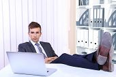 stock photo of table manners  - Businessman resting at his office with his shoes on table - JPG