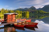 Beautiful red boat in a mountain lake Strbske Pleso, Slovakia, Europe