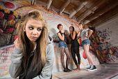 foto of peer-pressure  - Unhappy blond girl near cruel group of teens - JPG