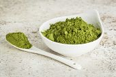stock photo of moringa oleifera  - moringa leaf powder in a small bowl with a spoon against a ceramic tile background - JPG