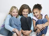 stock photo of tweeny  - Portrait of three cheerful young friends sitting side by side with knees tucked - JPG