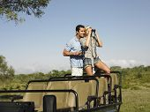 picture of  jeep  - Young couple on safari standing in jeep and looking through binoculars - JPG