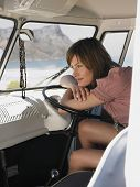image of campervan  - Happy young woman resting on steering wheel of van looking at view of mountains - JPG