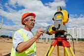 stock photo of theodolite  - One surveyor worker working with theodolite transit equipment at road construction site outdoors - JPG