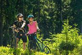 Mountain bikers standing and resting in forest sunny nature
