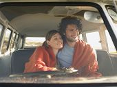 foto of campervan  - Loving young couple wrapped with blanket in front seat of campervan - JPG