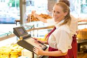 stock photo of cash register  - Cashier in a bakery posing with cash register - JPG