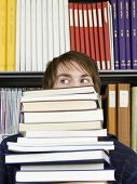 stock photo of shelving unit  - Closeup of a colleague student carrying stack of books in library - JPG