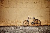 stock photo of color wheel  - Old rusty vintage bicycle near the concrete wall - JPG
