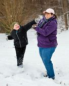 pic of snowball-fight  - Mother and son playing in snow by having snowball fight - JPG