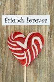 image of  friends forever  - Friends forever card with heart shaped lollipop on wooden surface - JPG