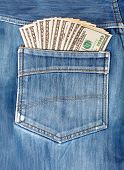 stock photo of denim jeans  - A hundred dollar bills sticking in the back pocket of denim blue jeans - JPG