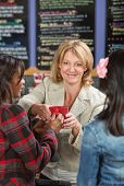 foto of cashiers  - Smiling restaurant cashier serving drinks to customers - JPG