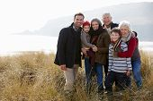 stock photo of dune  - Multi Generation Family In Sand Dunes On Winter Beach - JPG