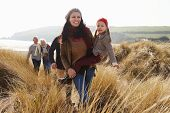 stock photo of multi-generation  - Multi Generation Family In Sand Dunes On Winter Beach - JPG