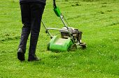 image of grass-cutter  - Gardener in action mowing green grass lawn with push mower  - JPG