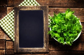 stock photo of chalkboard  - Black chalkboard for menu and fresh salad over wooden background. Diet Food Restaurant and healthy lifestyle concept. ** Note: Shallow depth of field - JPG