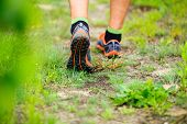 picture of crossed legs  - Sports shoes walking or jogging on green grass man runner cross country running on trail in summer forest - JPG