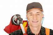 stock photo of trimmers  - Experienced gardener with trimmer and ear protectors - JPG