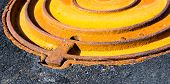 picture of manhole  - Rusty metal manhole cover in black asphalt surface - JPG