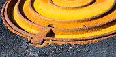 pic of manhole  - Rusty metal manhole cover in black asphalt surface - JPG