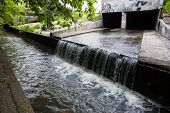 stock photo of underground water  - Water stream flowing out the underground tunnel into the Lybid river in Kyiv - JPG