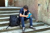 image of knapsack  - Sad Student with the Book on the landing steps - JPG