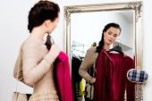 stock photo of showrooms  - Young woman choosing clothes in a showroom  - JPG