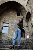 picture of gothic female  - Attractive tourist girl on vacation with a map in antique gothic city charming tourist woman studying a map standing in gothic quarter young female traveler searching right direction on city map - JPG