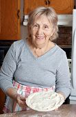 picture of grandma  - Happy senior woman or grandma showing homemade meat pie in her kitchen - JPG