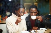 Постер, плакат: Friends at breakfast having coffee two young friends holding cups drink coffee in cafe