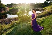 foto of maternity  - A beautiful back lit maternity portrait taken on the bank of a tropical south Florida lake with sun flare reflecting off of the water - JPG