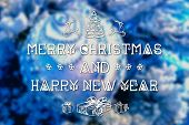 foto of blue spruce  - Merry Christmas and New Year hand drawing greeting card on blurred festive decoration ball or toy and spruce blue colored background - JPG