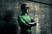 foto of cross-dressing  - Confident superhero standing with arms crossed against a concrete wall - JPG