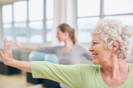 stock photo of virabhadrasana  - Close-up shot of elderly woman doing stretching workout at yoga class. Women practicing yoga at health club.