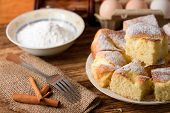 stock photo of curd  - Horizontal photo of Several portions of curd cake on white plate next two fork and cinnamon on jute cloth plus eggs and powder sugar in a bowl in background [[** Note: Shallow depth of field ** Note: Visible grain at 100%, best at smaller sizes - JPG