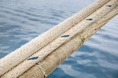 picture of dock  - Heavy duty and weathered ropes attached to the pier for secure docking of a ship - JPG
