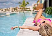 picture of infinity pool  - Woman in pink bikini relaxing by the pool - JPG