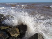 stock photo of gushing  - Waves upon rocks seascape photographed at Sidmouth in Devon - JPG