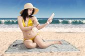 foto of suntanning  - Portrait of beautiful woman wearing bikini at beach and using suntan lotion on her skin - JPG