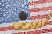 pic of hockey arena  - Hockey puck hockey stick and the image of the American flag on the ice - JPG