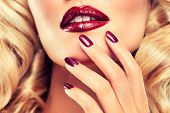 picture of perm  - Blonde model with curly Perm hair with Burgundy nails and lipstick - JPG