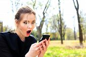 stock photo of stare  - Girl with disheveled hair and open mouth stares into the smartphone - JPG